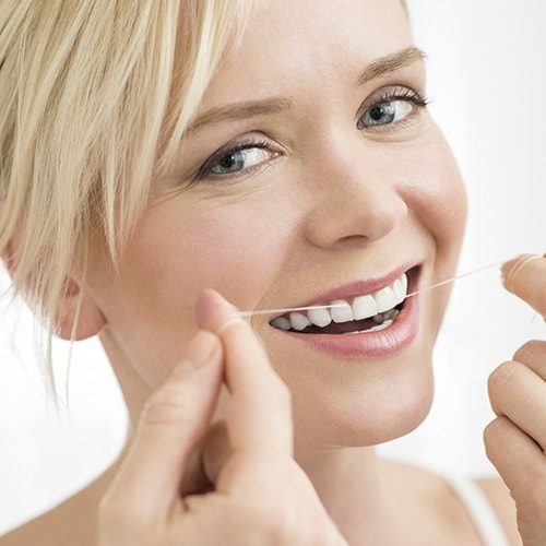 Blonde woman flossing her beautiful teeth, thanks to cosmetic dentistry