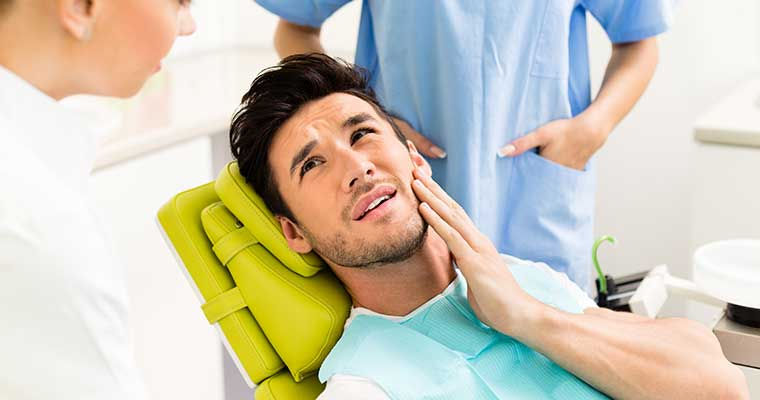 Young man experiencing a dental emergency holding his jaw in pain while laying in the dental chair.