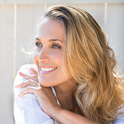 A middle-aged blond woman smiling with a youthful appearance from spa services at River Valley Dental.