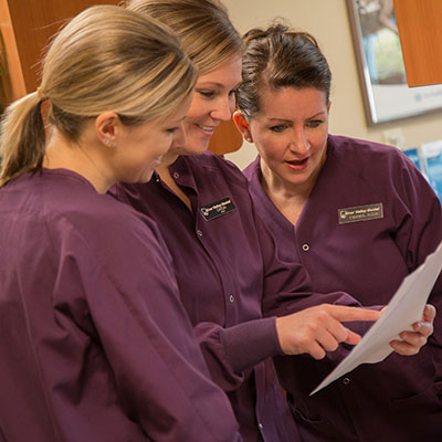 Three female team members at River Valley Dental looking at a patient report and smiling happily.